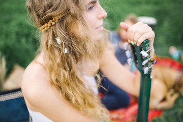 Young beautiful hippie curly hair woman with guitar outdoors