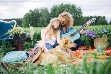 Young pretty hippie couple with guitar and dog outdoor