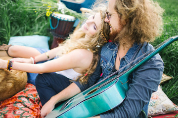 Young pretty curly hippie couple with guitar outdoor