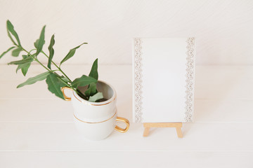 Green branches with leaves in cup and stylish paper for notes on