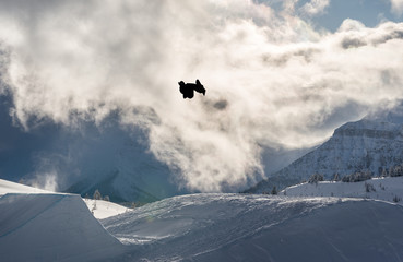 Snowboarder performing flip off a large jump in the mountains