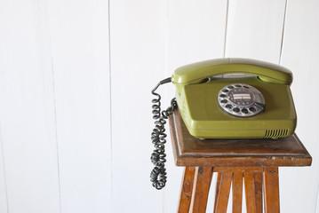 Retro rotary telephone on wood vintage table. White background