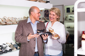 Mature couple picking shoes in boutique.
