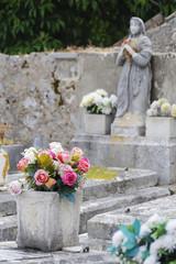 Klagende Figur am Friedhof mit Blumen im Vordergrund