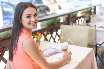 Pretty girl drinking coffee in cafeteria