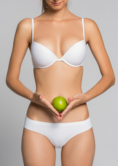 Beautiful woman body and green apple. Conceptual image of dieting healthy lifestyle