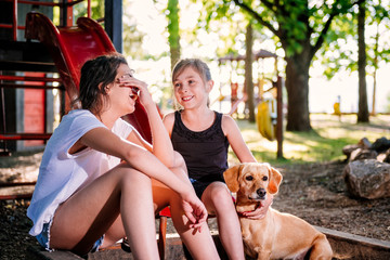 Two talking girls and dog on a playground in summer