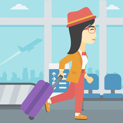 Woman walking with suitcase at the airport.