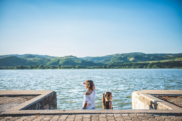Two girls standing on river dock and looking sideways