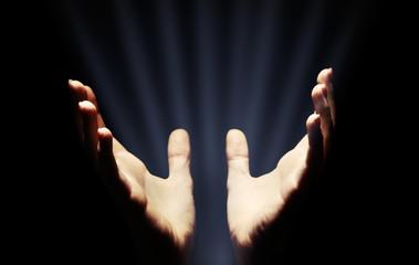 Female hands with light on dark background