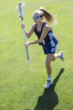 Action photo of a cute female Lacrosse player running with her lacrosse stick