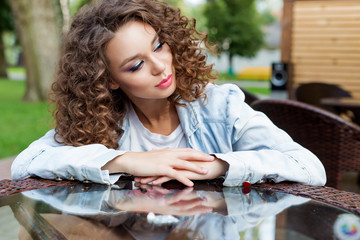 beautiful young girl with curly hair sits at a table at an outdoor cafe summer day