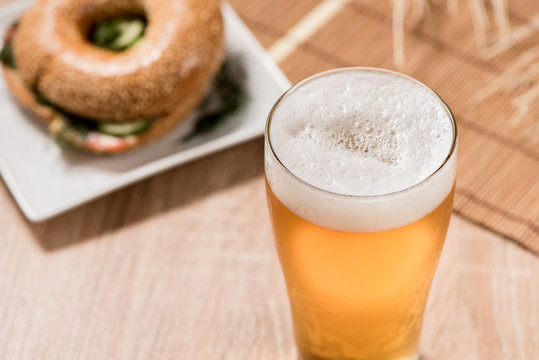 beer in glass and burger on wood table