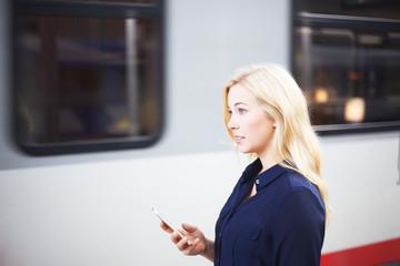 Woman at platform using her phone
