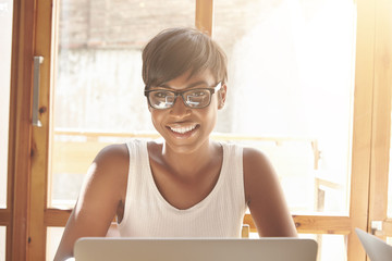 Beautiful portrait of dark-skinned woman with pixie cut. Shinny smile and intelligent look of a young girl with laptop make this shot so positive and inspire to productive and comfortable job at home.
