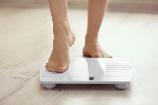 Female leg stepping on floor scales