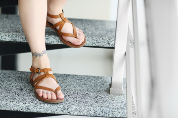 Female feet with tattoo on staircases