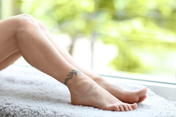 Female feet with tattoo on blurred street background