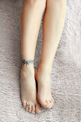 Female feet with tattoo on carpet