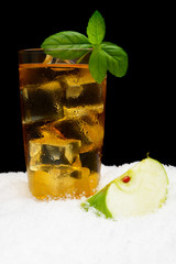 Apple juice,ice cubes and apple with mint on black on snow
