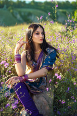 beautiful girl eastern appearance sits among flower fields at sunset, fashionable toning, creative color