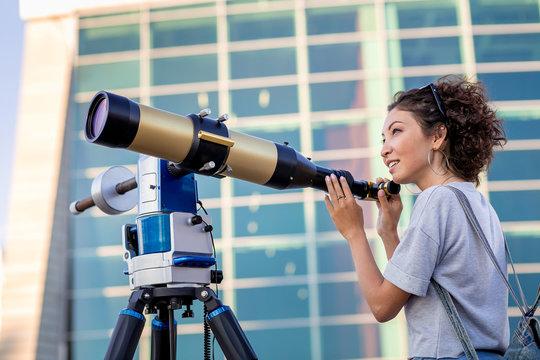 girl looking through a telescope outdoors