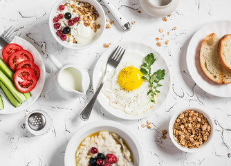 Assortment of breakfast - fried egg, fresh vegetables, oatmeal with berries, cottage cheese, yogurt and berries, homemade granola on a light table. Healthy food. Top view