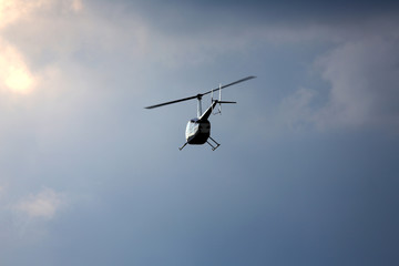 Helicopter in cloudy blue sky