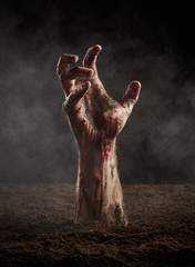 Male hand in dirt and blood on dark background
