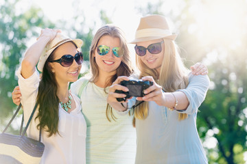 Friends taking picture at summer holidays, girls with camera taking self-portrait on their travel vacation