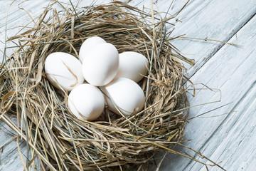 White chicken eggs in straw nest