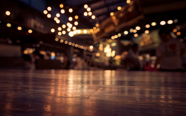 Empty wood table top on blur cafe restaurant in dark background