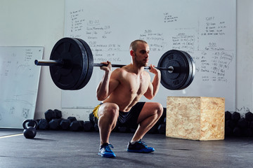 Barbell squat exercise - athletic man during weightlifting worko