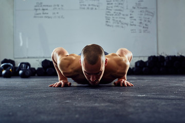 Dark picture of athlete doing pushups at the gym