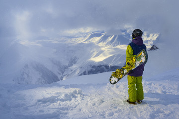 snowboarder standing and looking at  mountains in snowy weather