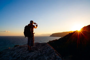 landscape photographer traveler man on cliff above the sea in summer rays of setting sun is studying  compositional structure of frame