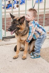 TEL AVIV, ISRAEL. May 6, 2014. Caucasian little boy with a german shepherd dog.