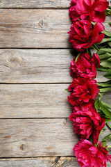 Bouquet of red peony flowers on a grey wooden table