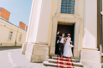 Stylish gorgeous bride and elegant groom walking out of church, happy newlyweds