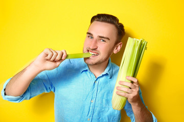 Handsome man eating celery on yellow background