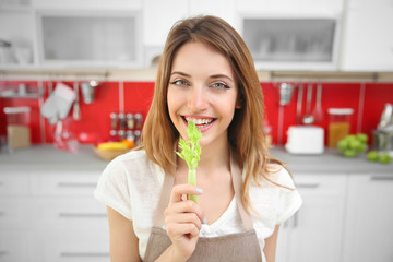 Beautiful girl eating celery in kitchen