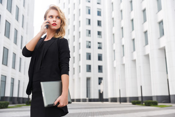 Business woman holding laptop and talking on phone