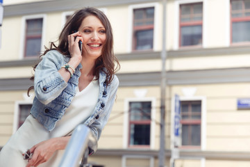 Brunette girl with long hair talking on phone and smiling