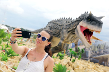 Girl makes a selfie against the background of the layout dinosaur