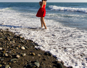 Beautiful young happy girl wearing red dress playing with the waves on a beach.