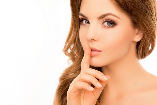 Pretty woman having secret and holding finger on lips