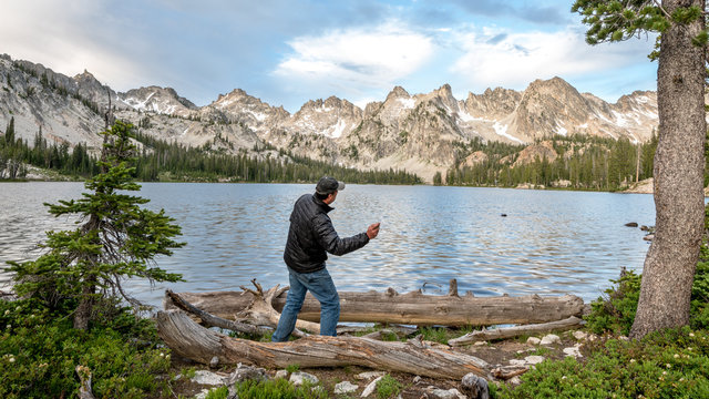 Man prepares to skip a rock on a mountain lake
