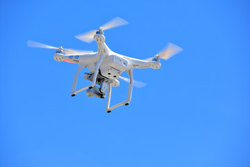 Wall Mural - white drone with video camera in blue sky