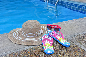 woman hat with sunglasses and flip-flops by swimming pool