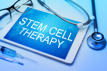 stem cell therapy word on tablet screen with medical equipment on background